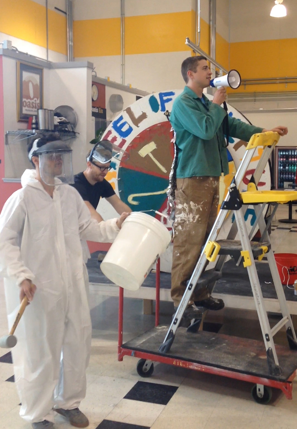 person with megaphone on a ladder, person with black glasses behind him with face-shield up, person in white jumpsuit with hammer and bucket wearing plastic face-shield