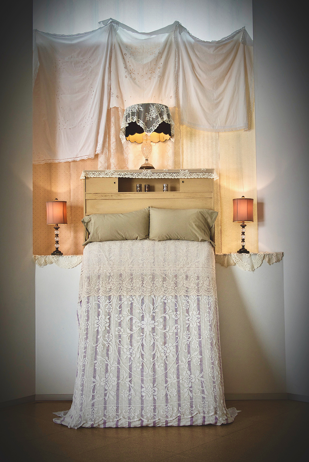 Bed upright on wall with lace coverlet, pillows, headboard, three lamps and window covering