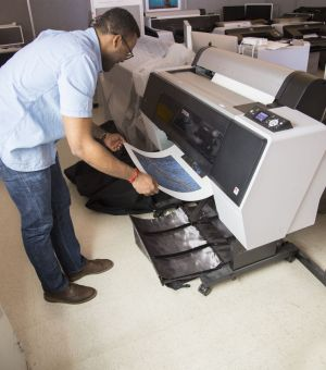 A student removing a photograph from a printer