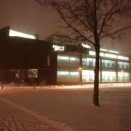 The north facade with its glass exterior wall during an evening winter snow.