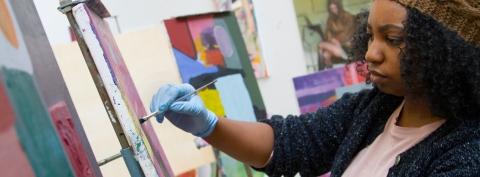 A painting student works on her painting.