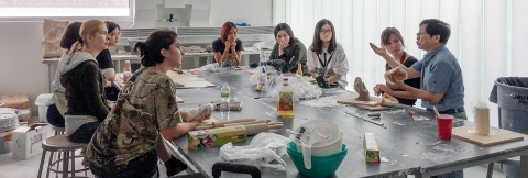 Undergraduate students in discussion with an Art Professor.