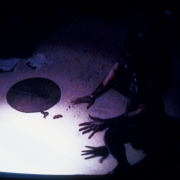 A close-cropped TV screen shows a downward view of the floor under a spotlight. The hands of a silhouetted figure reach in towar