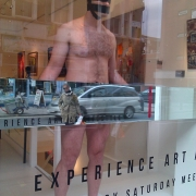 The bald, naked figure of a male artist stands in a storefront gallery window.  The artist's hands and midsection are concealed