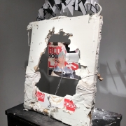 """A 28"""" x 36"""" piece of drywall is tilted up on a black table. It is wrapped in white t-shirts, styrofoam, plaster, floss, etc.; a"""