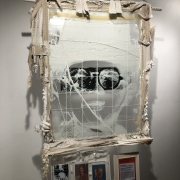 """A 32"""" x 40"""" frame hangs from the ceiling. The contents are removed so the white pen drawing of a boy's face on the glass is tran"""