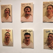 """A close-up shot from a previously featured art work: the white male portraits of an artist are scrawled with """"alcoholic, meth he"""
