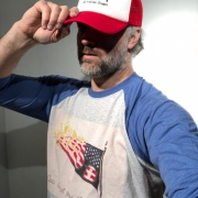 A bearded, white, male figure tips his hat to conceal his eyes. His red hat and 3/4-sleeve shirt are each printed with a burning