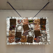 metal grid hanging from ceiling, with 24 mixed media pieces attached to the grid in 4 rows 6 columns